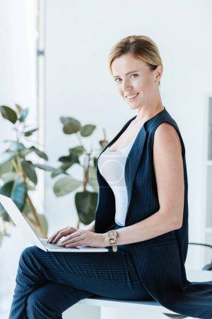 Photo pour Belle femme d'affaires assis sur la table et travailler avec l'ordinateur portable au bureau - image libre de droit