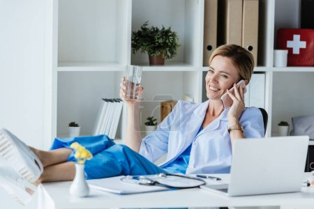 smiling female doctor with legs on table drinking water and talking on smartphone in office