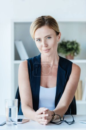 Photo for Portrait of attractive adult businesswoman looking at camera and sitting at table in office - Royalty Free Image