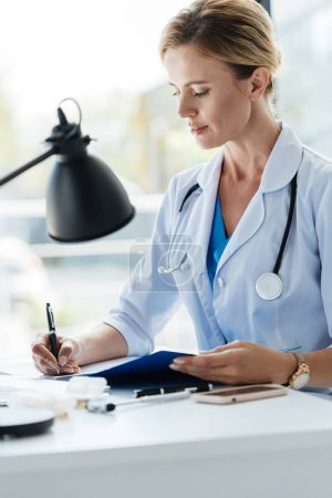 Photo for Confident adult female doctor in white coat with stethoscope writing in clipboard at table in office - Royalty Free Image
