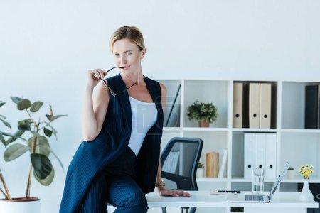Photo pour Belle femme d'affaires adulte tenant des lunettes et posant sur la table avec ordinateur portable au bureau - image libre de droit