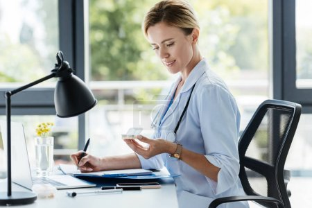adult female doctor writing in clipboard and holding pills at table in office