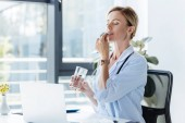 adult female doctor in white coat holding glass of water and taking pill at table with laptop in office