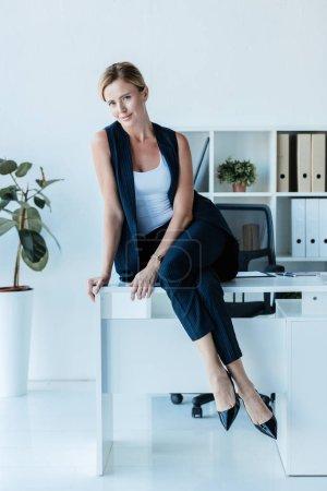 belle femme adulte posant sur la table au bureau