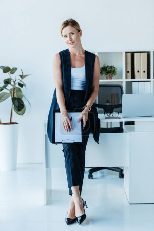 Photo for Adult businesswoman standing with clipboard near table with laptop in office - Royalty Free Image