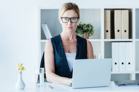 serious adult businesswoman in eyeglasses working with laptop at table in office