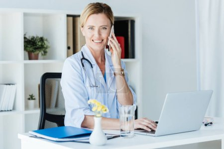 happy female doctor looking at camera and talking on smartphone at table with laptop in office