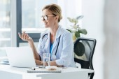 adult happy female doctor in eyeglasses talking at table with laptop in office