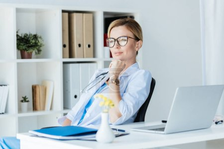 pensive adult female doctor in eyeglasses sitting at table with laptop in office