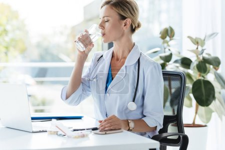 adult female doctor in white coat with stethoscope over neck drinking water at table in office