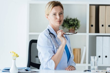 attractive female doctor in white coat with stethoscope over neck holding eyeglasses at table in office