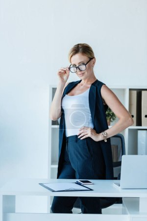 adult businesswoman adjusting eyeglasses and looking at camera near table with laptop in office