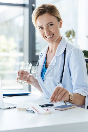 smiling female doctor holding glass of water and taking pill at table in office