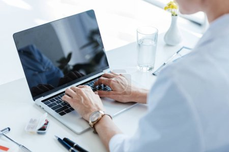 partial view of female doctor typing on laptop with blank screen at table in office