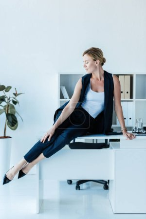 adult businesswoman looking away and posing on table in office