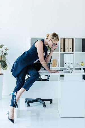 side view of beautiful businesswoman in eyeglasses working with laptop at table in office