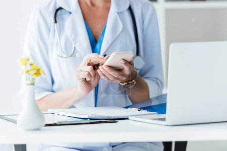 cropped image of female doctor using smartphone at table with laptop in office