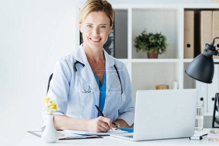 adult female doctor with stethoscope over neck writing in clipboard at table with laptop in office