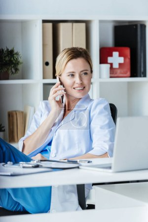 female doctor looking away and talking on smartphone at table with laptop in office