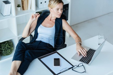 Photo for High angle view of businesswoman using laptop at table with smartphone and clipboard in office - Royalty Free Image