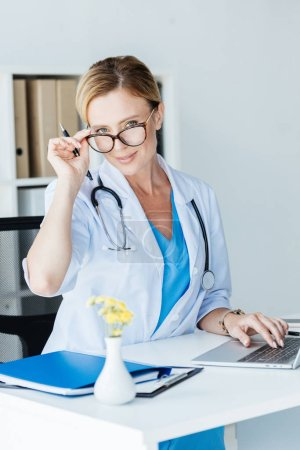 attractive adult female doctor in eyeglasses looking at camera while working on laptop at table in office
