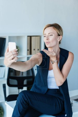 attractive adult businesswoman blowing air kiss during video call on smartphone in office
