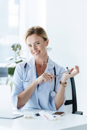 happy female doctor with stethoscope and reflex hammer at table in office