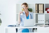 adult female doctor in eyeglasses smelling flowers at table with laptop in office