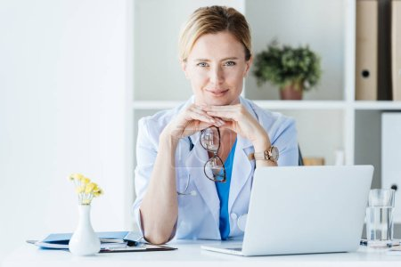 Photo for Smiling female doctor in eyeglasses looking at camera at table with laptop in office - Royalty Free Image