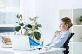 side view of thoughtful female doctor with legs on table sitting in office