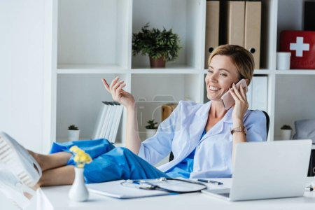 smiling female doctor gesturing by hand and talking on smartphone with legs on table in office