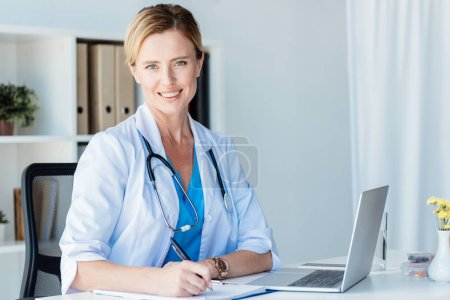 smiling female doctor looking at camera while writing in clipboard at table with laptop in office