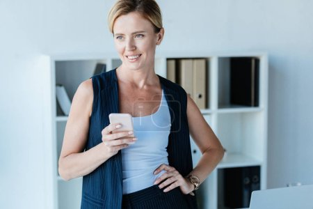 confident smiling businesswoman holding smartphone and looking away in office
