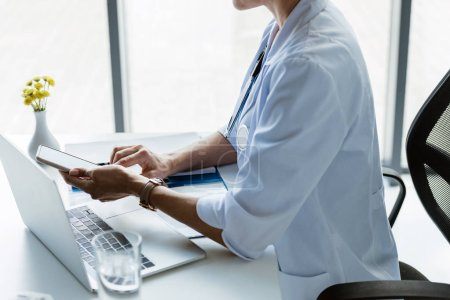 partial view of female doctor using smartphone at table with laptop in office