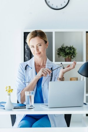 smiling female doctor in white coat holding reflex hammer at table with laptop in office