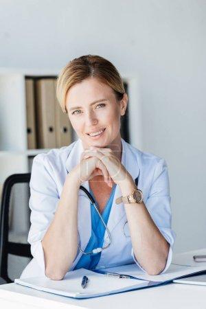 Photo pour Séduisante femme médecin en manteau blanc avec stéthoscope au-dessus du cou regardant la caméra à la table au bureau - image libre de droit