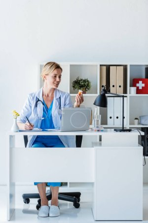 female doctor writing and holding pills at table with laptop in office