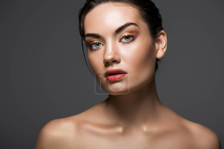 attractive nude model with makeup posing isolated on grey