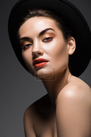 attractive model with makeup posing in elegant felt hat, isolated on grey
