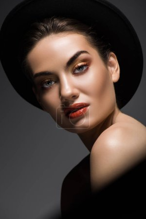 attractive sensual woman with makeup posing in black felt hat, isolated on grey