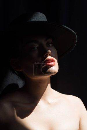 beautiful stylish girl in black felt hat posing in dark