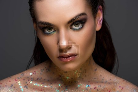 glamorous fashionable girl posing with glitter on body, isolated on grey