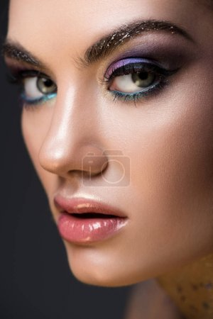 close up of young model with glitter makeup on face, isolated on grey
