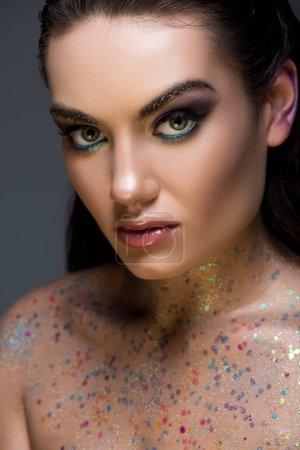 Photo pour Séduisante modèle glamour, posant avec des paillettes sur le corps, isolé sur fond gris - image libre de droit