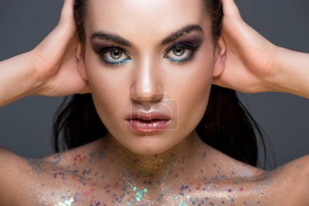 glamorous woman with makeup and glitter on body, isolated on grey