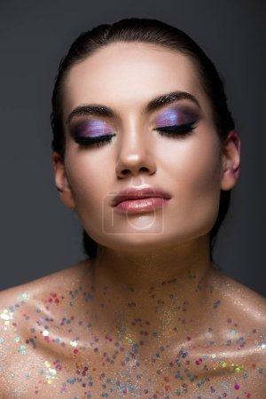 attractive glamorous girl with closed eyes and glitter makeup, isolated on grey