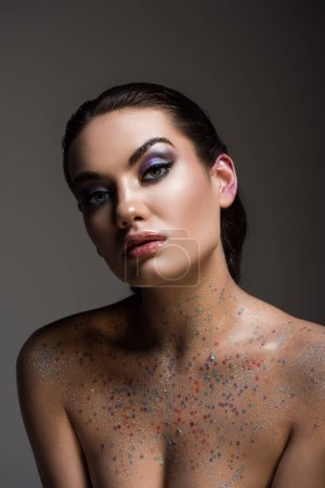 glamorous young woman posing with glitter on body, isolated on grey