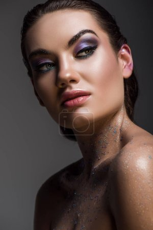 glamorous girl posing with glitter on body for fashion shoot, isolated on grey