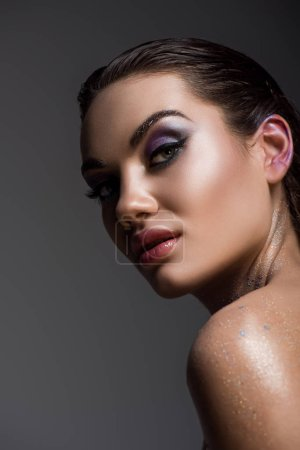 beautiful young woman with glitter makeup, isolated on grey