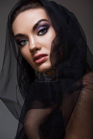 beautiful stylish woman posing in black veil, isolated on grey